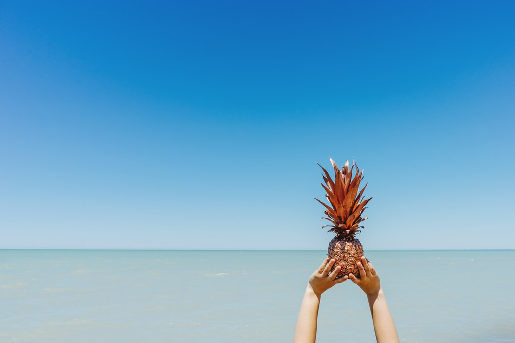 A person holding a pineapple up to a blue sky.