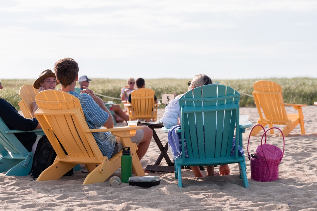 People sitting in chairs on the beach.