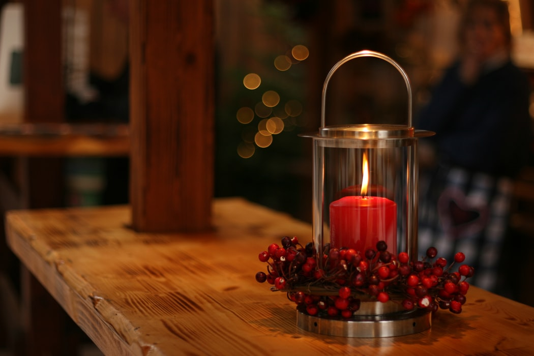 A cozy lit candle sitting on a wooden bar.