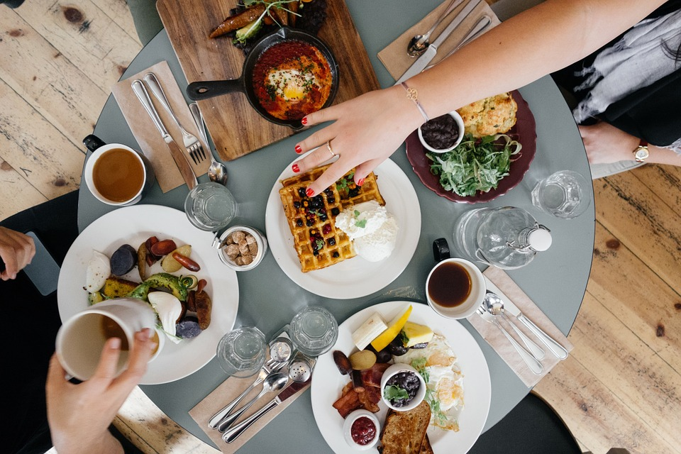 A group of people eating various brunch foods around a table.