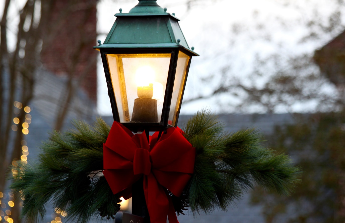 A street light with a garland and red bow.