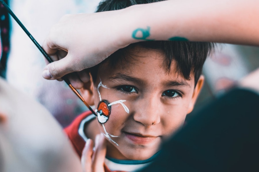 A kid getting their face painted.